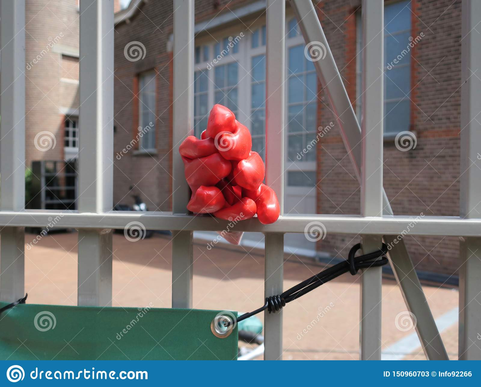 Pair of red plastic working gloves between the bars of a fence