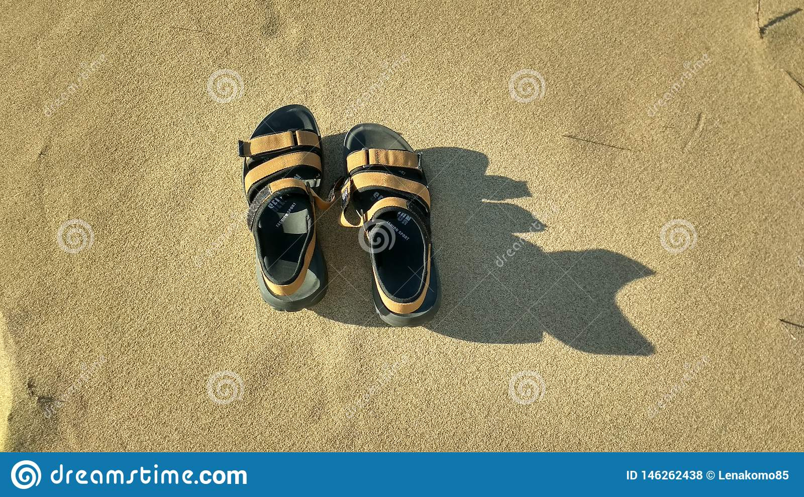 A pair of sandals on the sand.