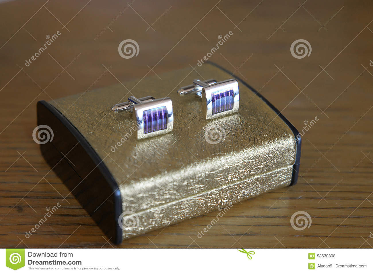 A pair of silver, platinum or white gold cuff links with blue enamel positioned on an elegant golden box