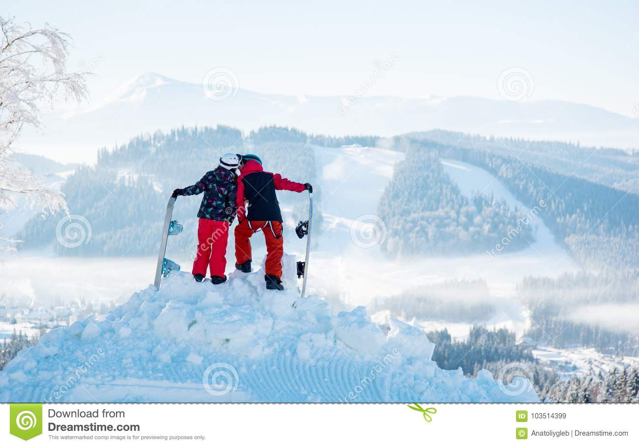pair snowboarders kiss on top of mountain. back view stock image