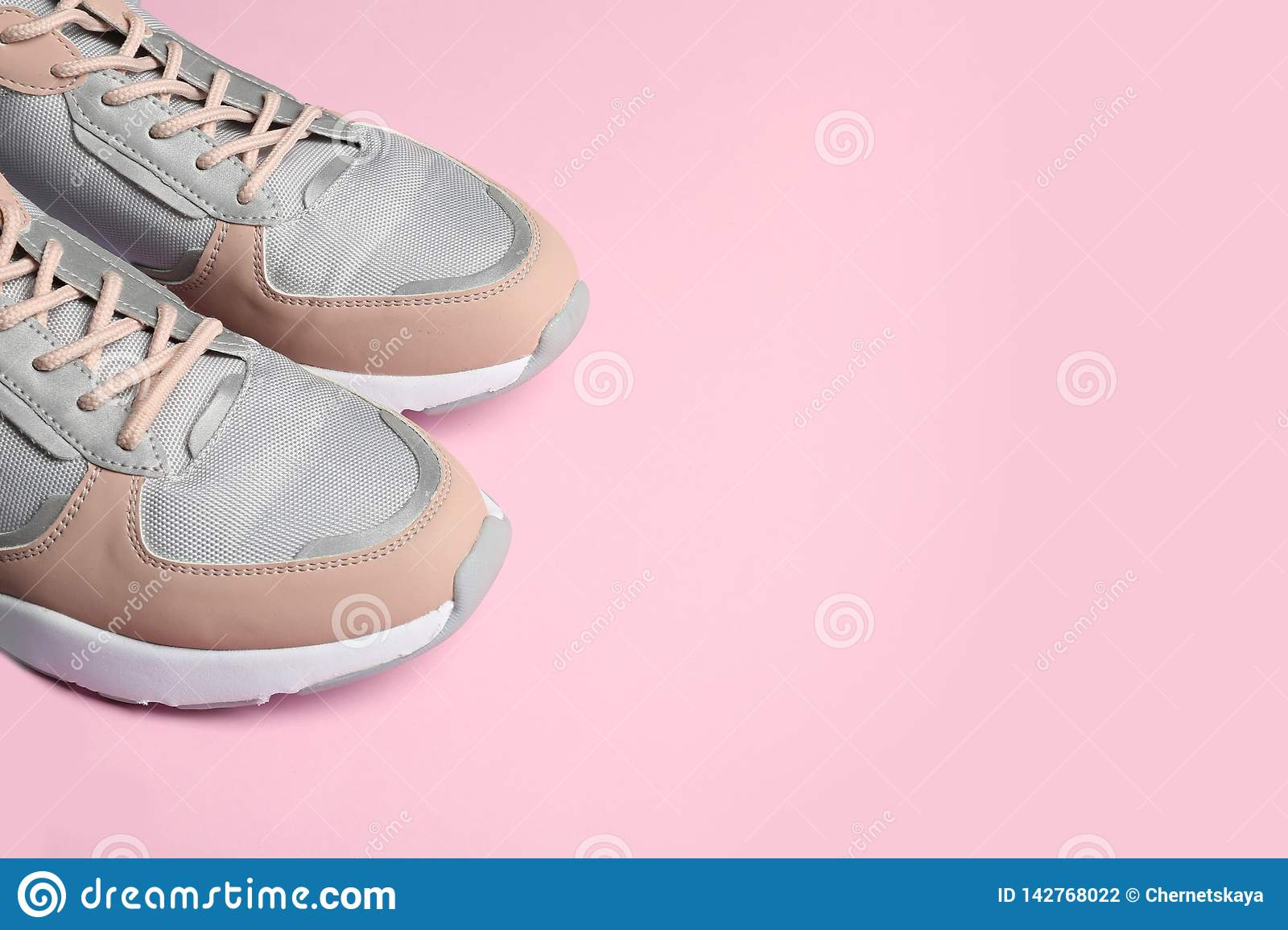 Pair of sports shoes on color background, closeup