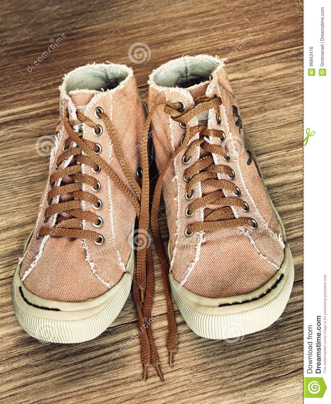 Pair of Trendy Gym shoe on wooden background taken closeup.