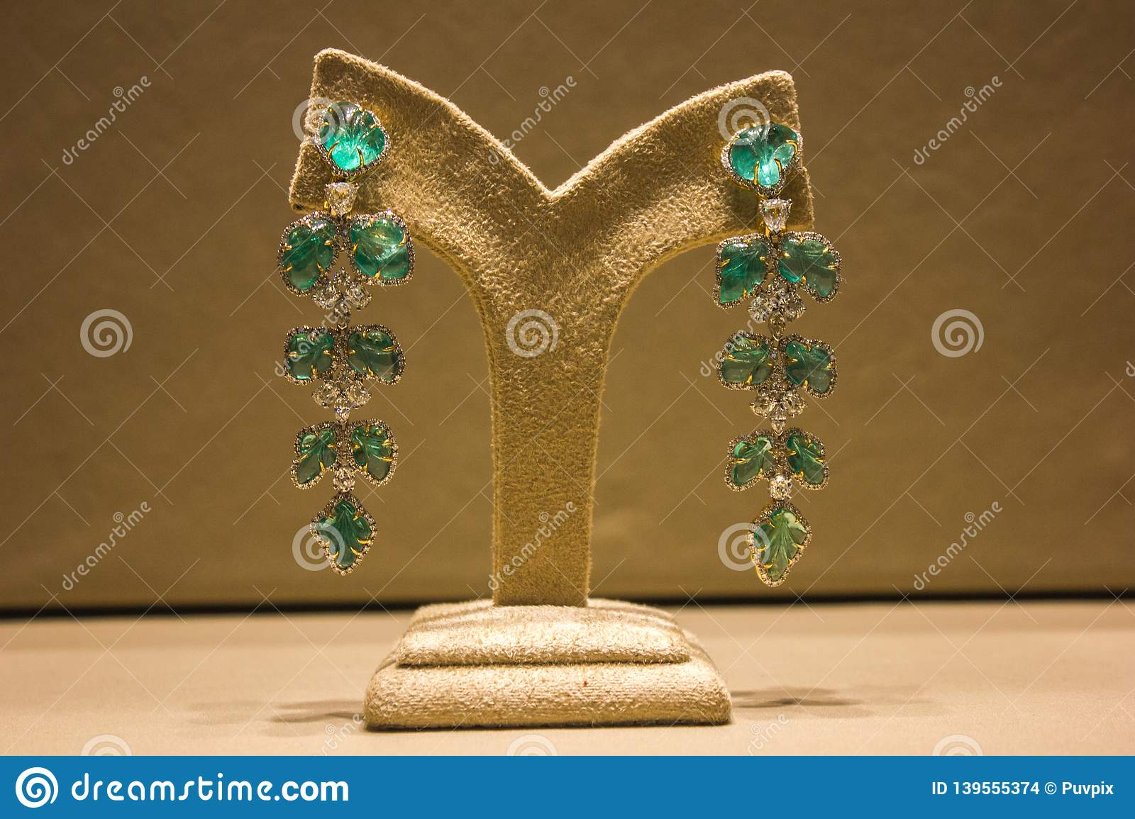 Turquoise earrings ,pair of long ones with white stones displayed in a velvet stand with a beige velvety background