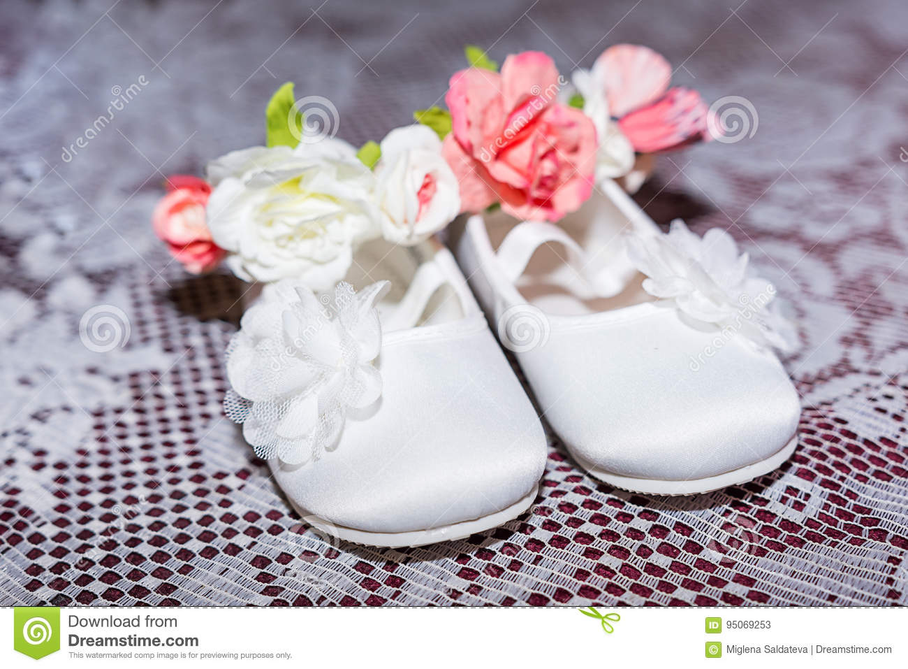 Pair of white baby shoes on pants and shirt at Christening Baptism Ceremony  at church 5916db699572