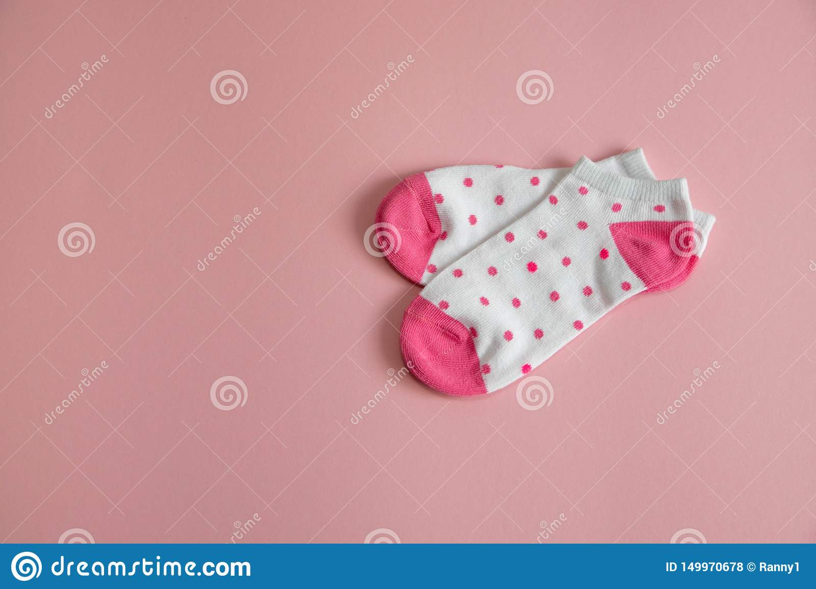 A pair of white socks for children with pink socks and heels, with pink dots, on a pink background. Socks for girls