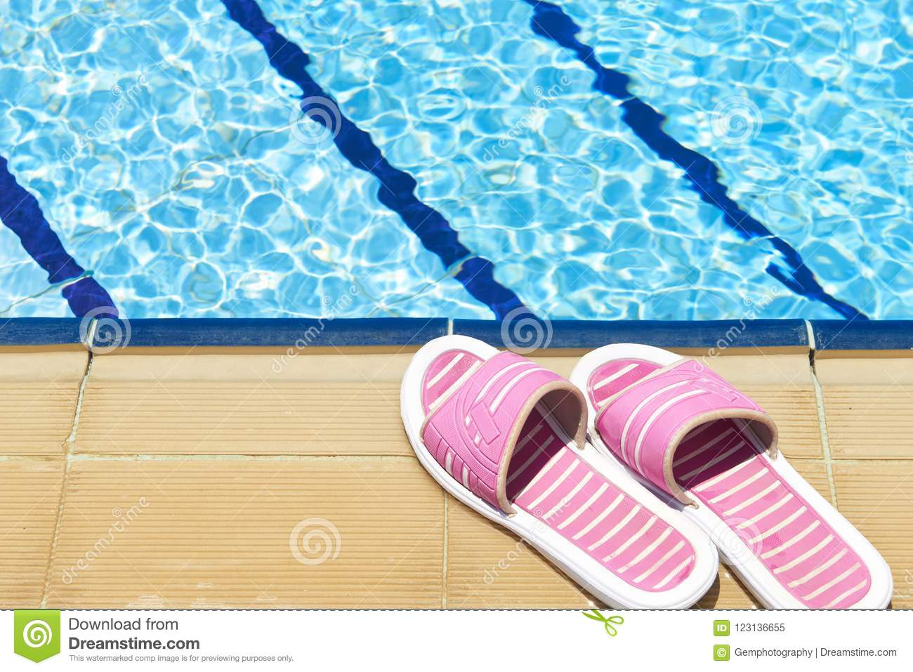 af27254a7215a A pair of womens plastic sandals by side of swimming pool