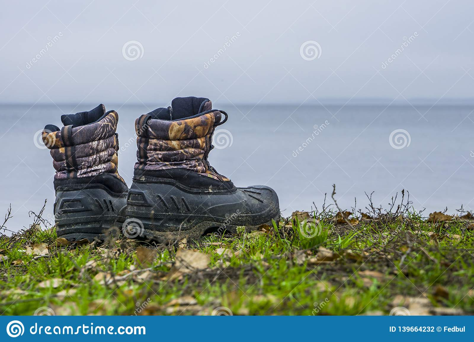 A pair of worn hiking boots on natural background. Dirty boots for hiking, fishing, traveling