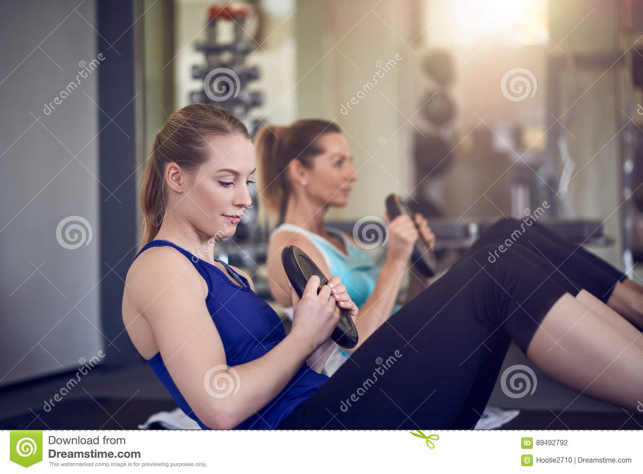 Pair of young adult women doing abdominal muscle exercises