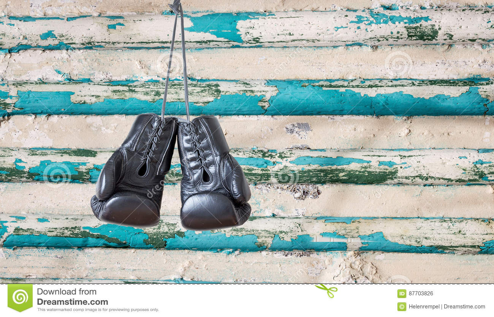 Paires de gants de boxe noirs accrochant sur un vieux mur en bois rustique