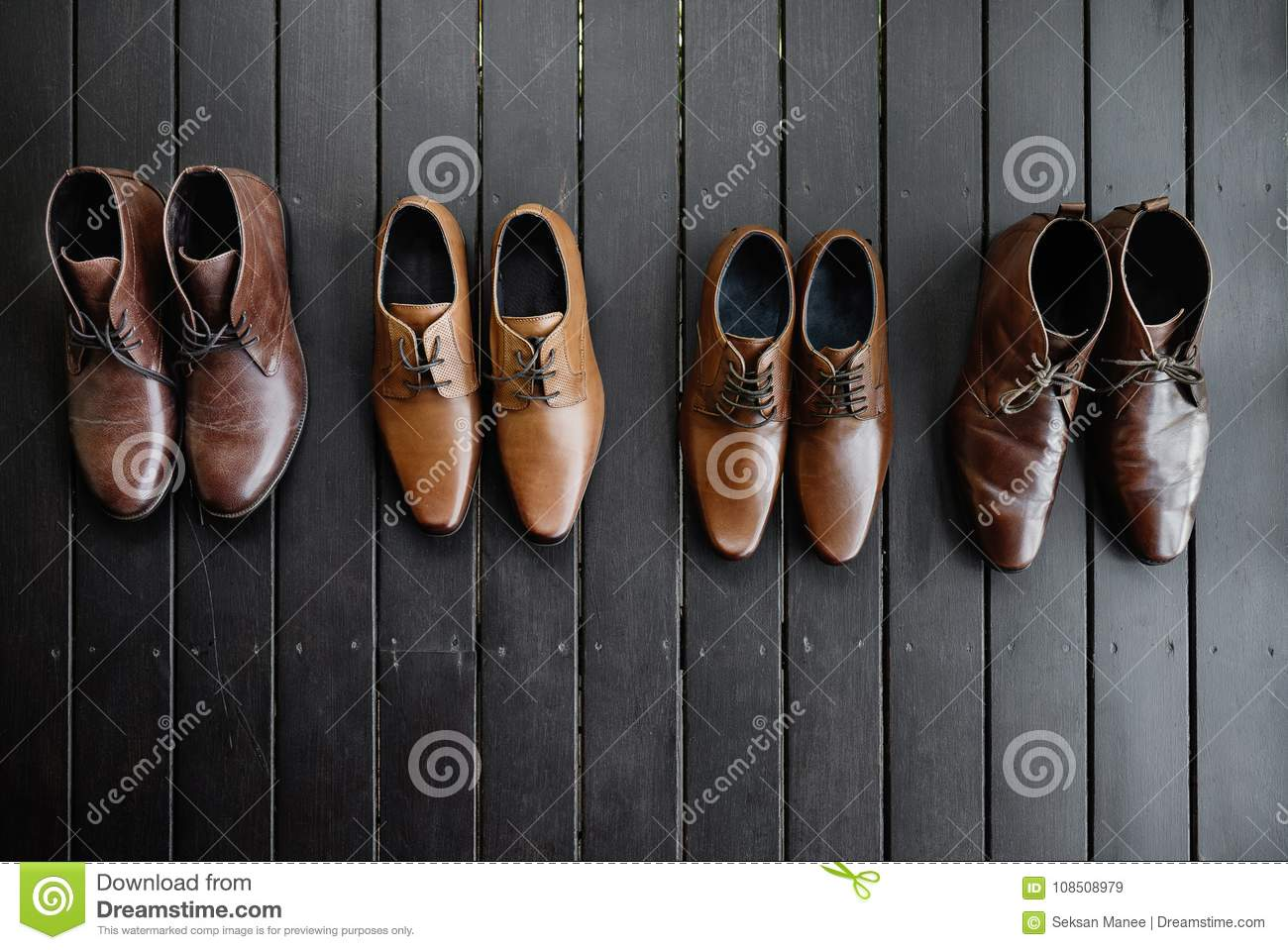 4 pairs of men's brown shoes on the black wooden floor