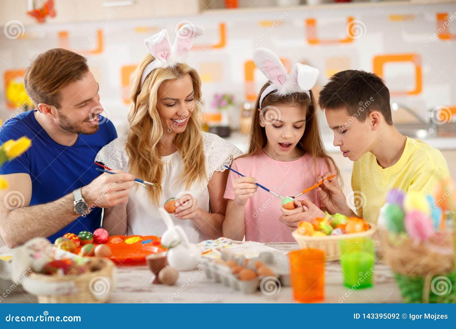 Pais com as crianças que pintam ovos coloridos