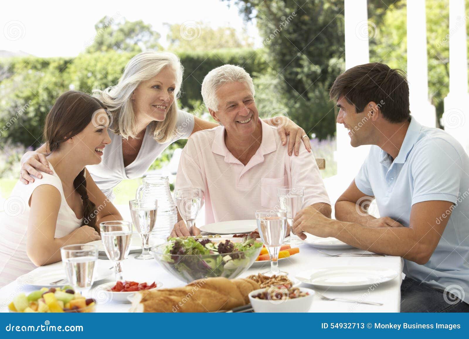 Pais e crianças adultas que apreciam Al Fresco Meal