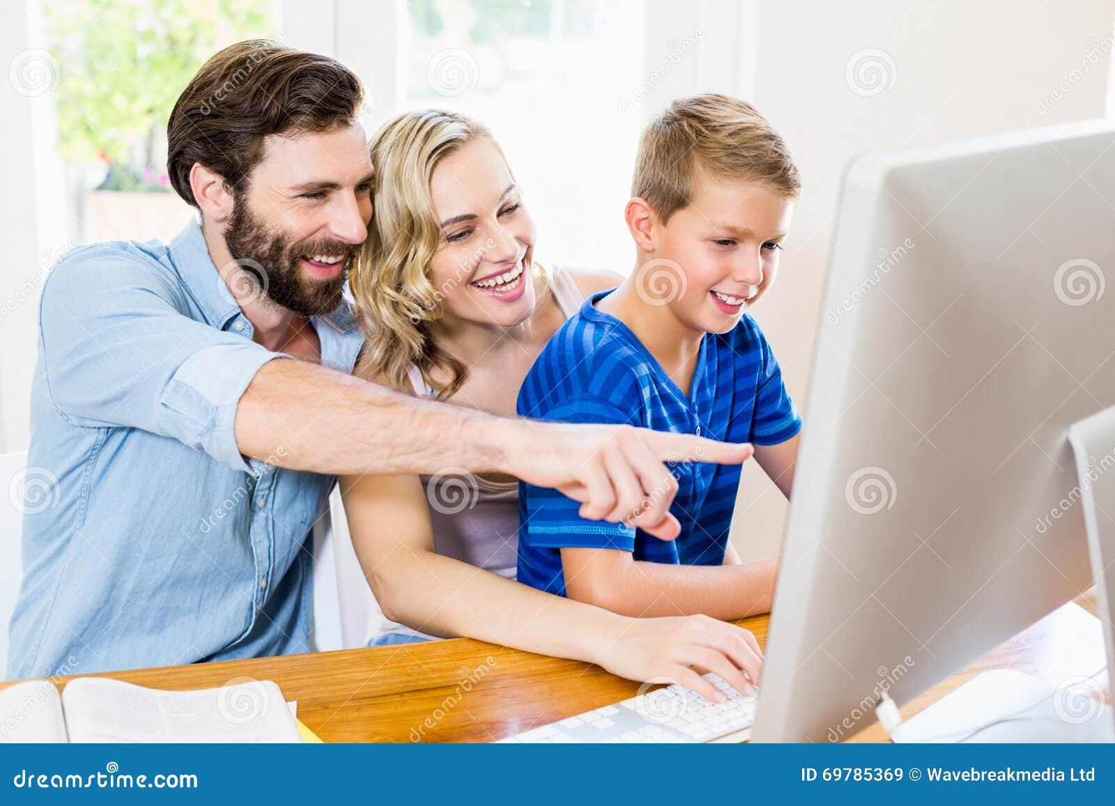 Pais e filho que usa o computador na sala de visitas