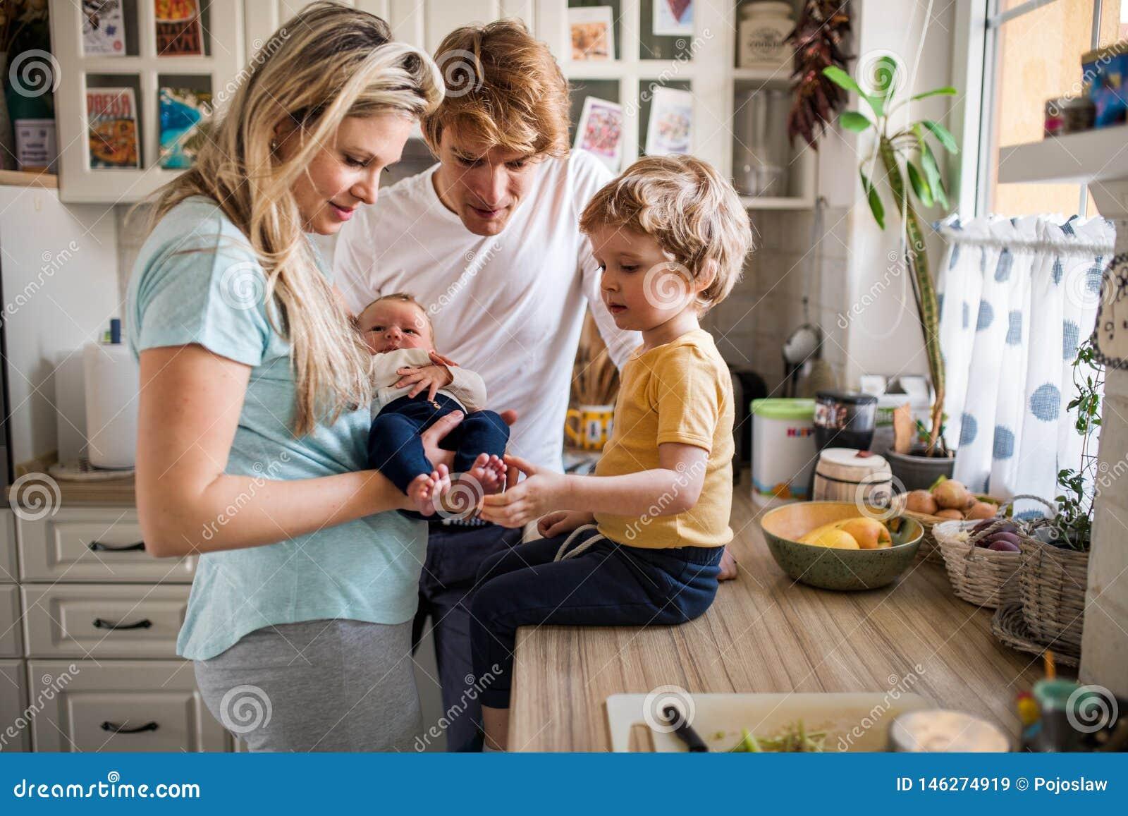 Pais novos com beb? rec?m-nascido e o filho pequeno da crian?a em casa