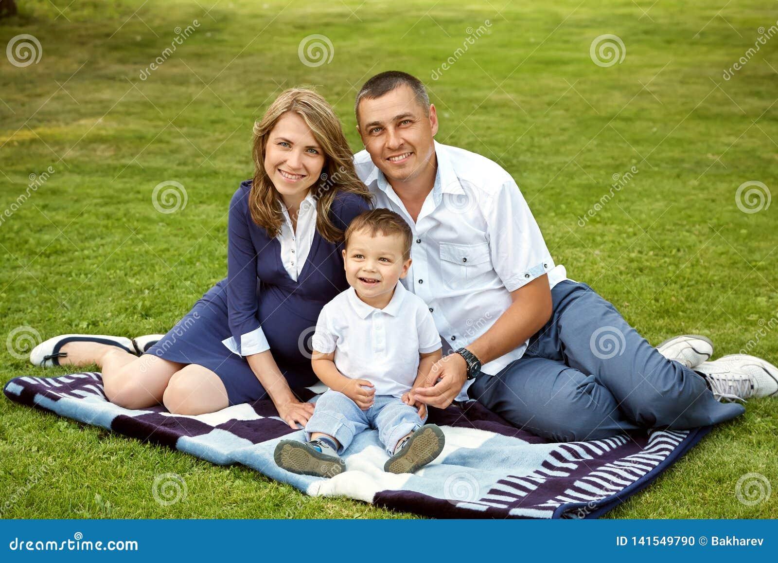Pais novos com o filho no verão Mamã, paizinho e criança