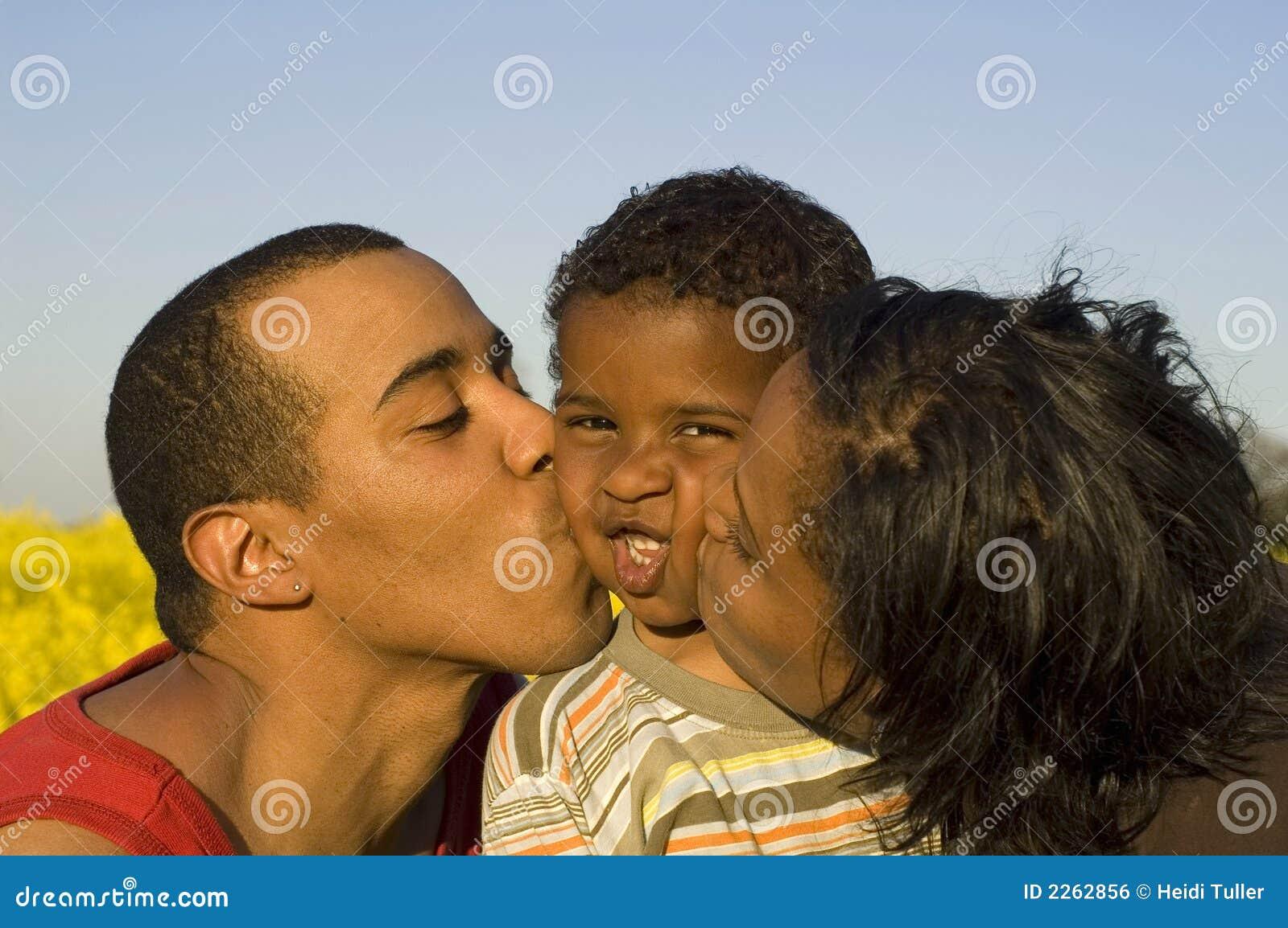 Pais que beijam seu filho