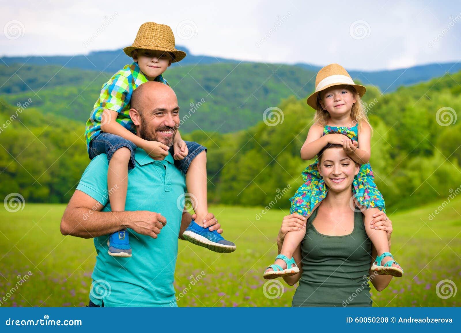 Pais que dão às cavalitas o passeio às crianças, família feliz