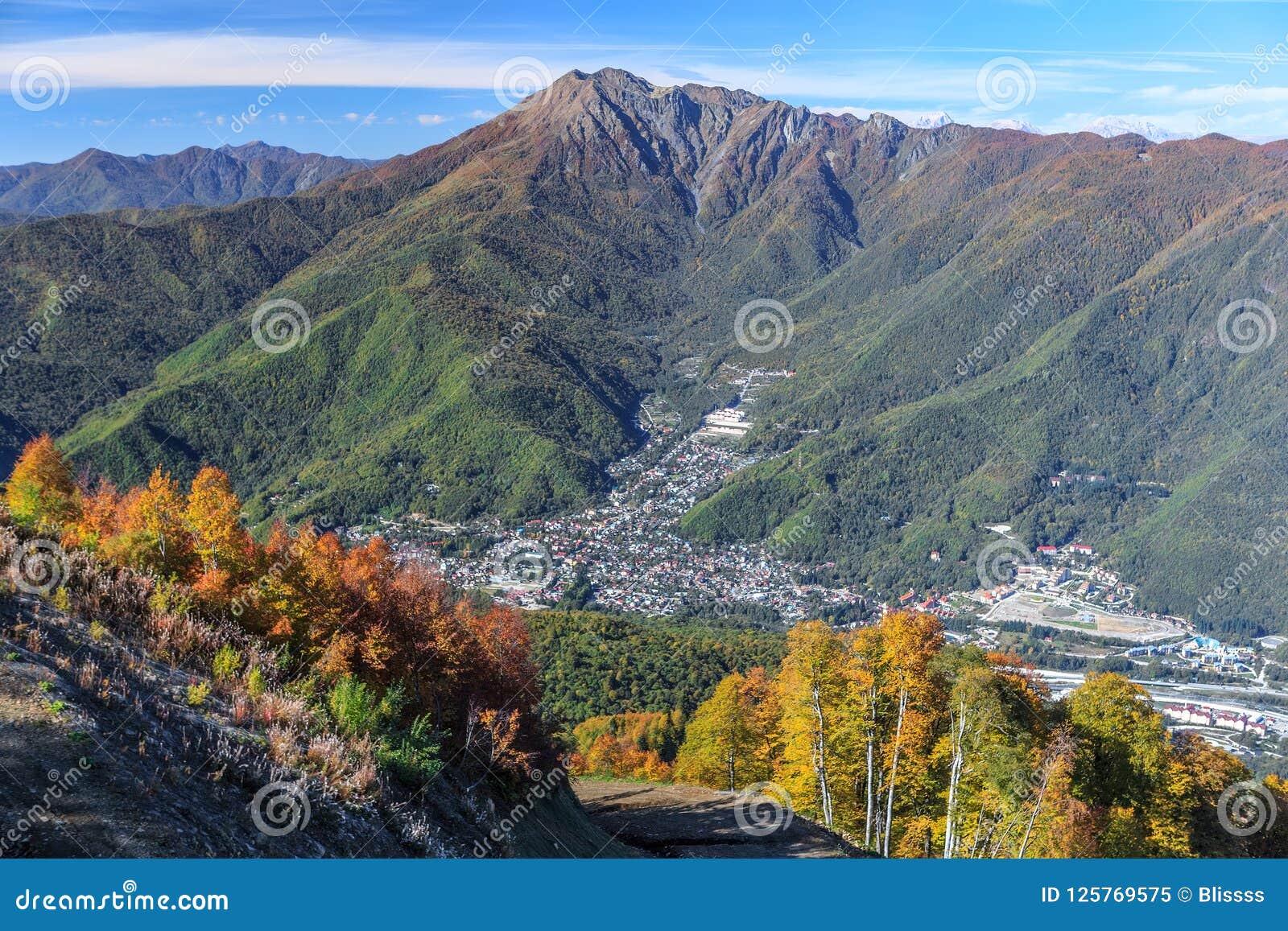 Paisagem aérea ensolarada cênico da montanha do céu azul do outono da vila de Krasnaya Polyana em Sochi, Rússia com pico de Achis
