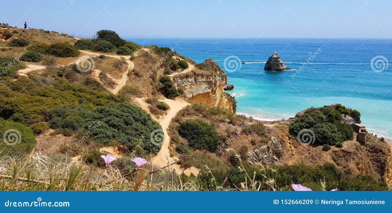 Paisagem bonita: caminhando trajetos em penhascos rochosos perto do Praia Dona Ana da praia, Lagos, Portugal