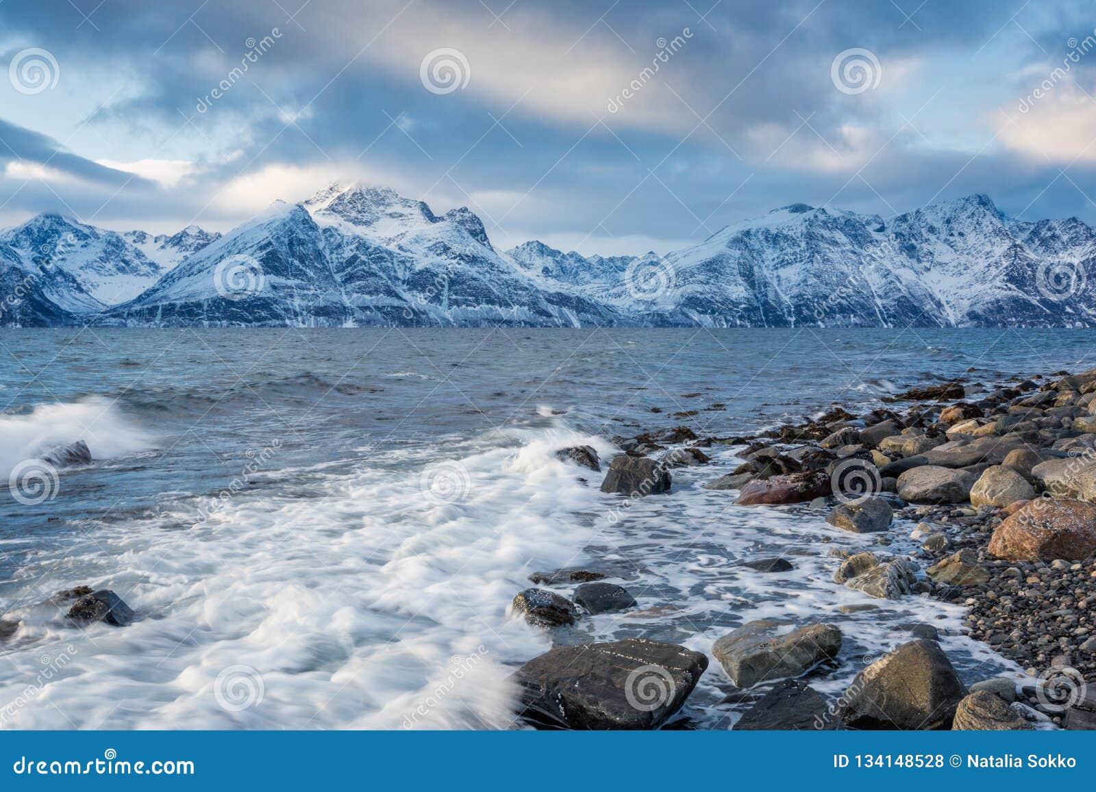 Paisagem bonita do inverno com litoral rochoso e montanhas