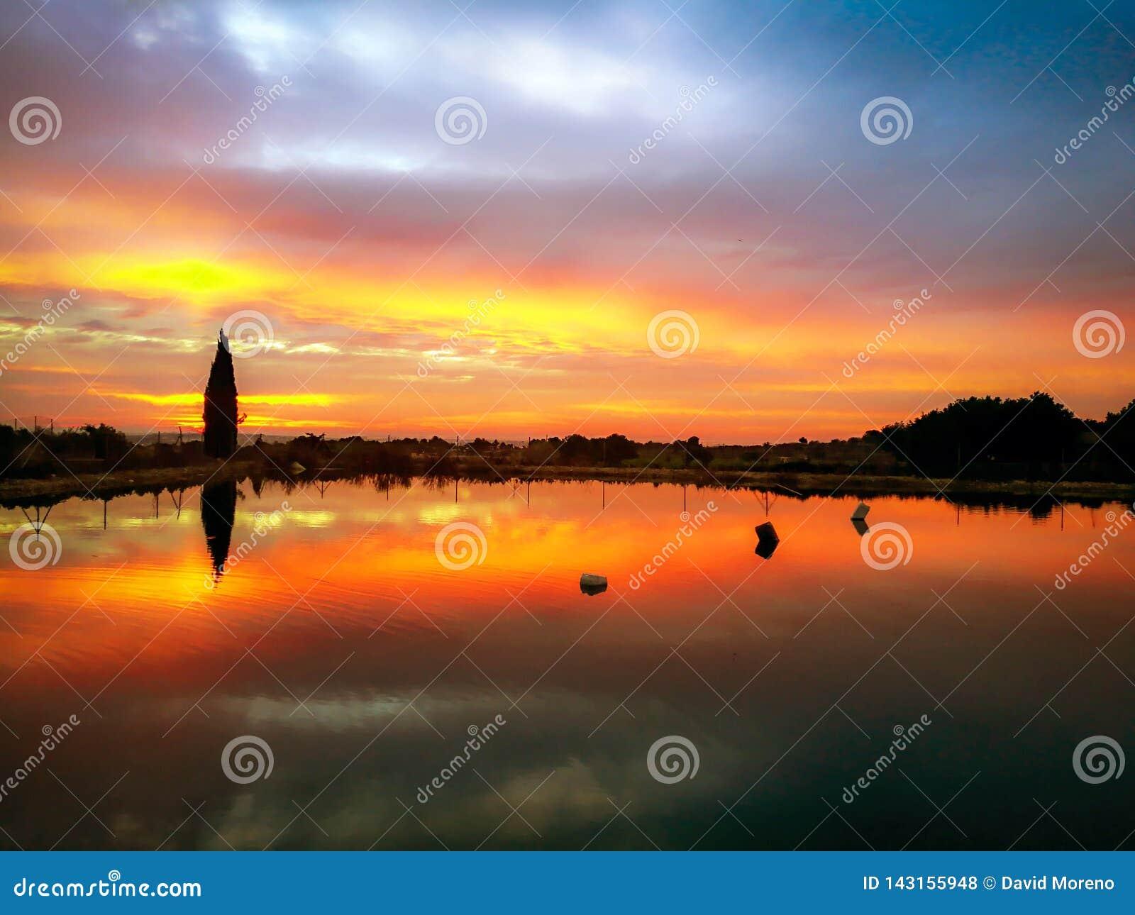 A paisagem bonita do por do sol refletiu em um lago sobre as montanhas