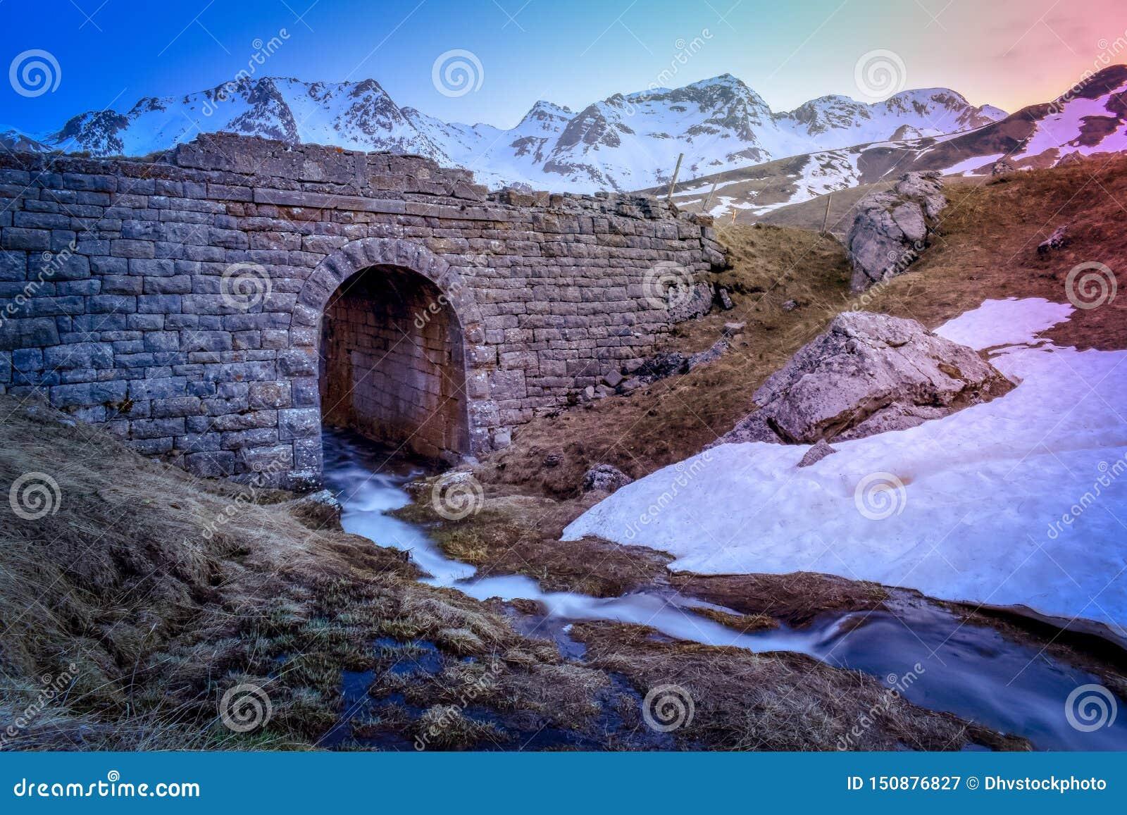 Paisagem da cachoeira do córrego da montanha e ponte no por do sol, Pyrenees