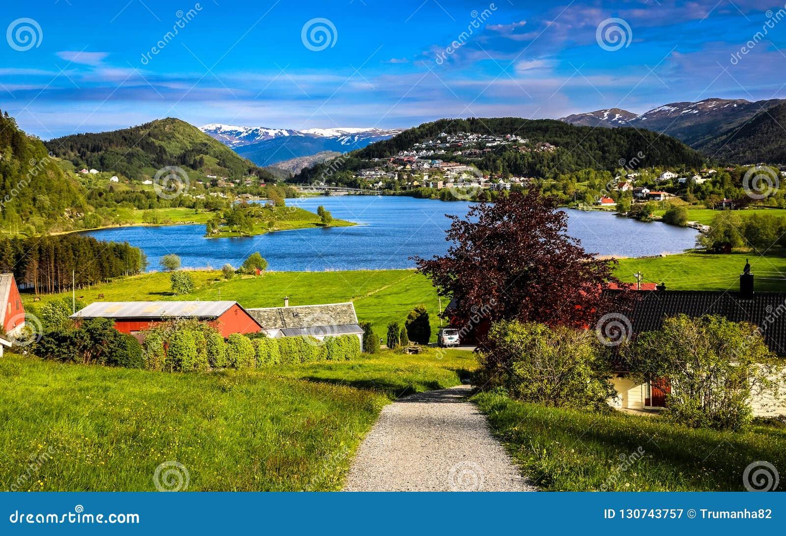 Paisagem da mola com vista geral de um vale tranquilo com prados verdes, um lago Coração-dado forma e as casas da exploração agrí