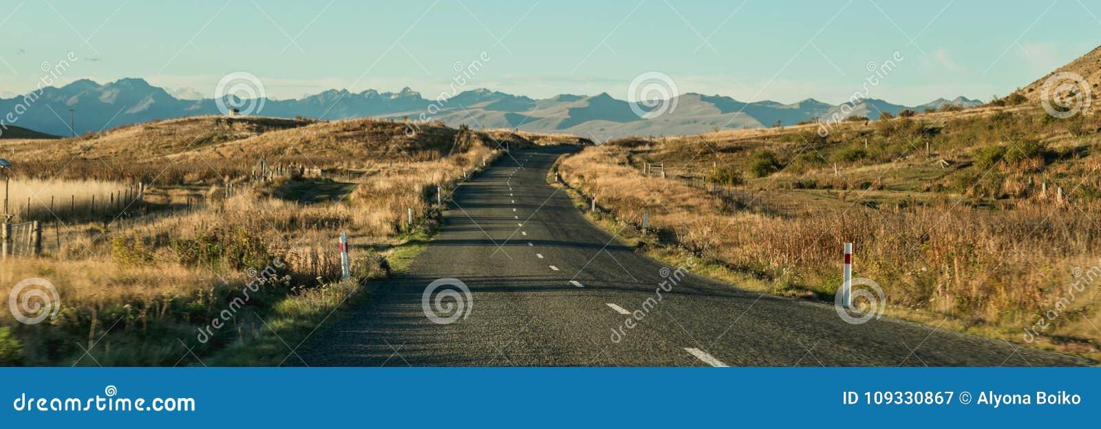 Paisagem da montanha com estrada e o céu azul, Otago, Nova Zelândia
