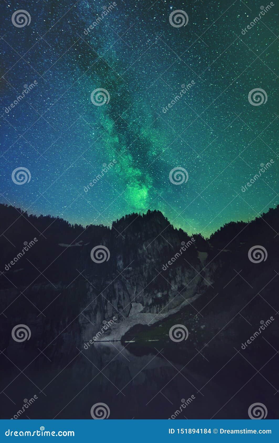 Paisagem da montanha com a Via Látea visível atrás dela