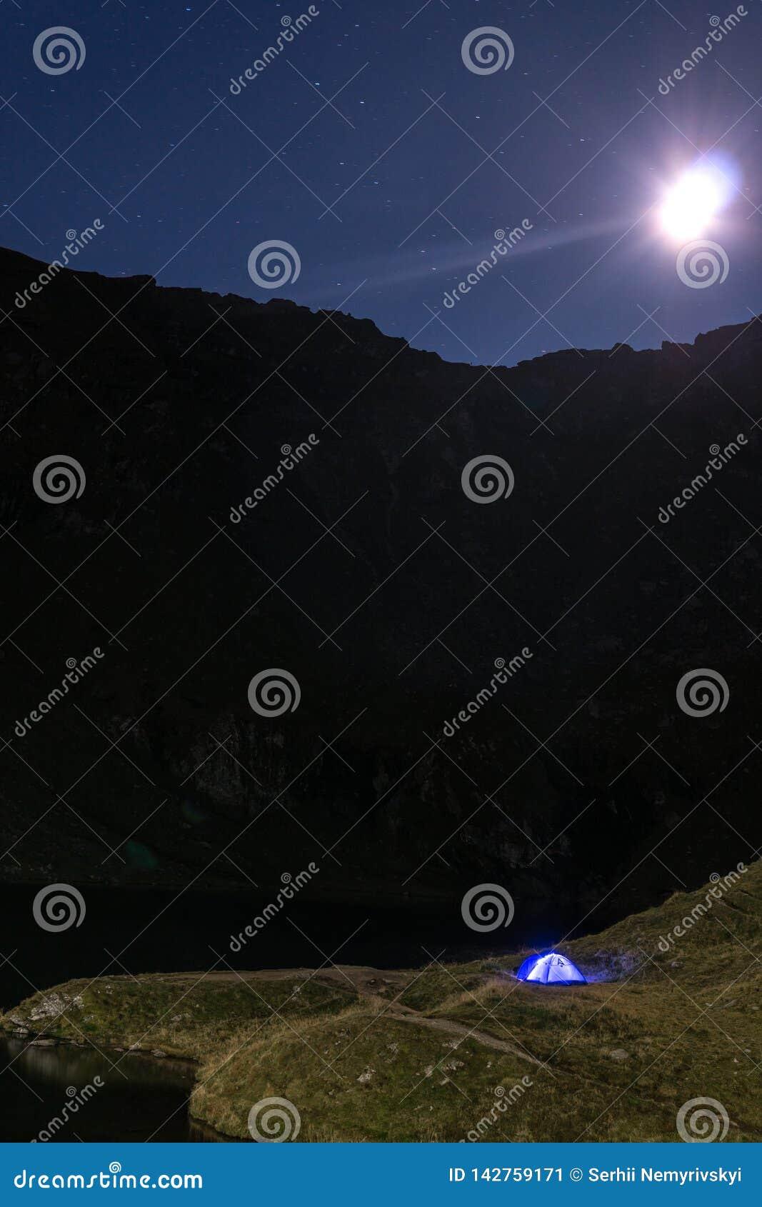 Paisagem da montanha da noite com a barraca azul iluminada Picos de montanha e a lua exterior no lago Lacul Balea, Transfagarasan