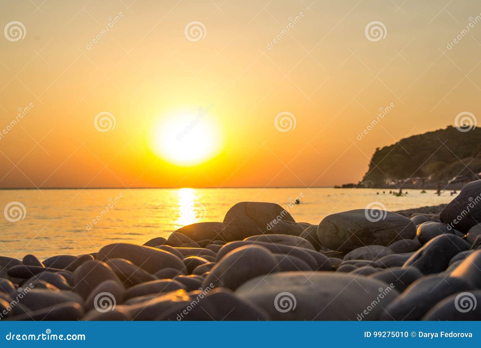 Paisagem de ardência bonita do por do sol no Mar Negro e no céu alaranjado acima dele como um fundo