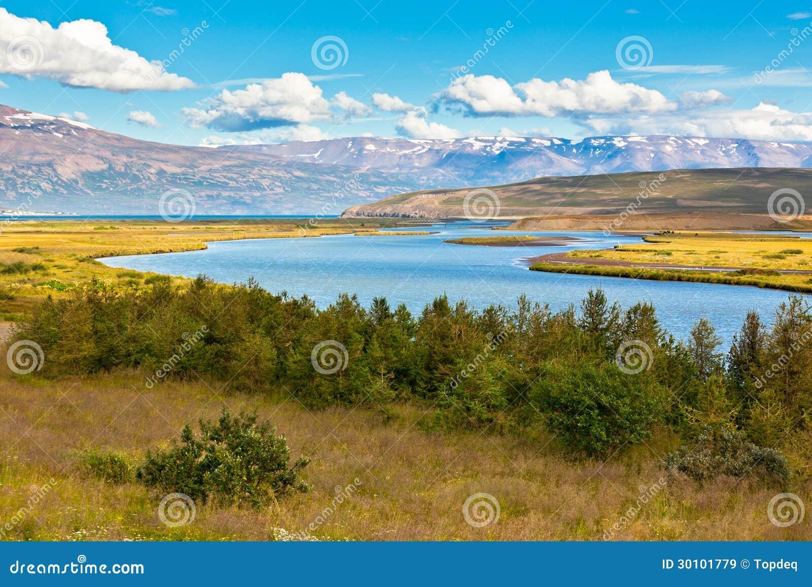 Paisagem de Islândia do verão com rio, montanhas e o céu azul ...