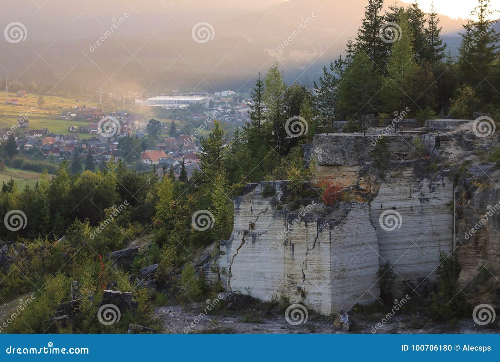 A paisagem de mármore da pedreira do outono fotografou no por do sol com uma cidade no fundo