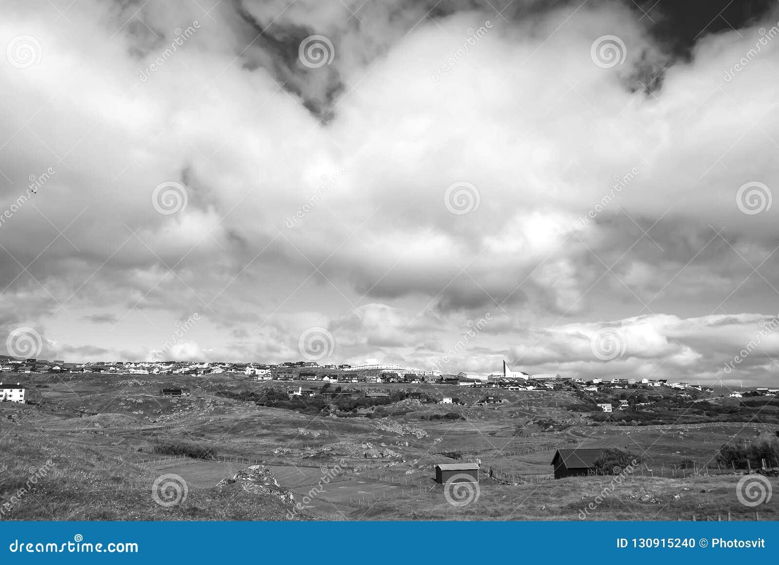 Paisagem do país com as casas da quinta sob o céu nebuloso em Torshavn, Dinamarca Opinião bonita da paisagem Terreno montanhoso c