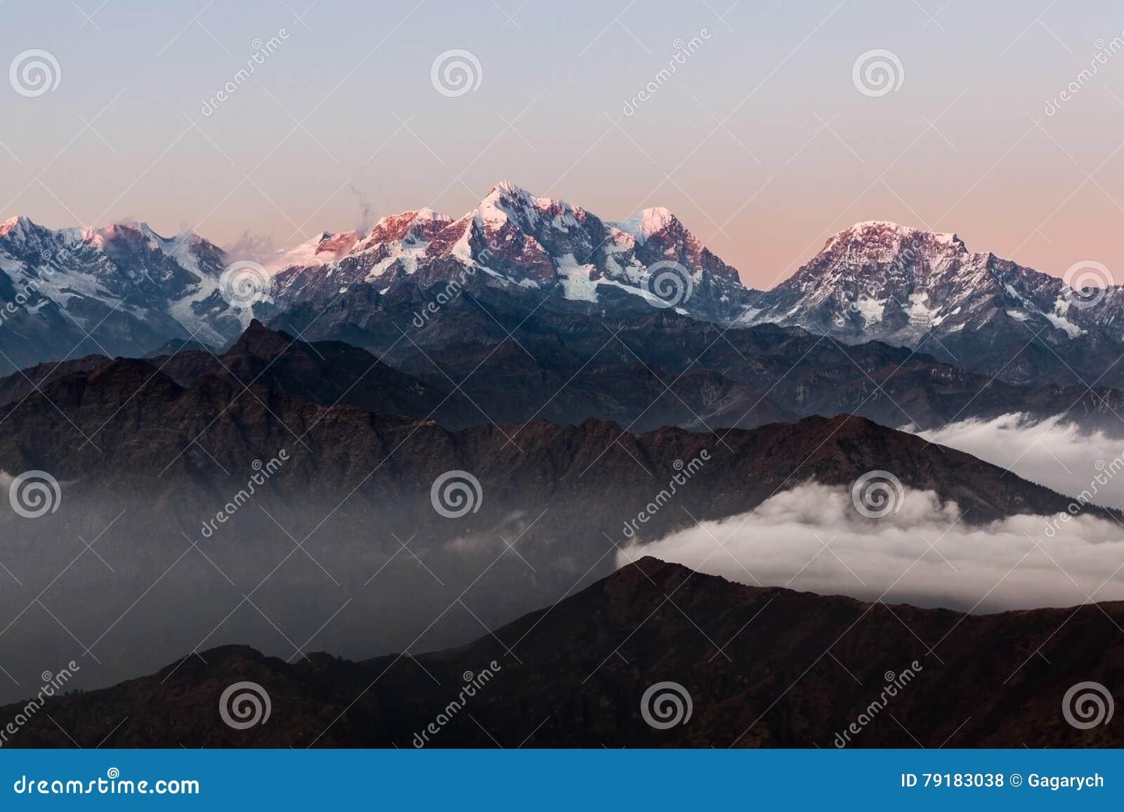 Paisagem dramática com os picos nevado que aumentam acima