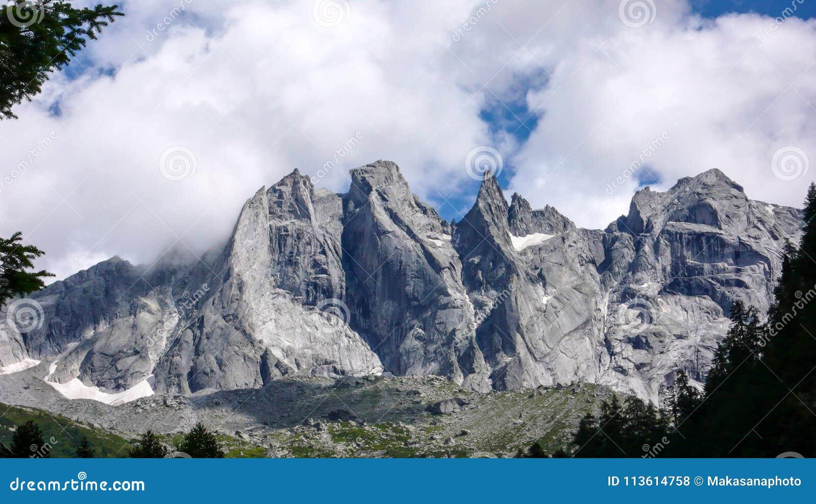 A paisagem fantástica da montanha nos cumes suíços com granito afiado irregular repica sob um céu nebuloso