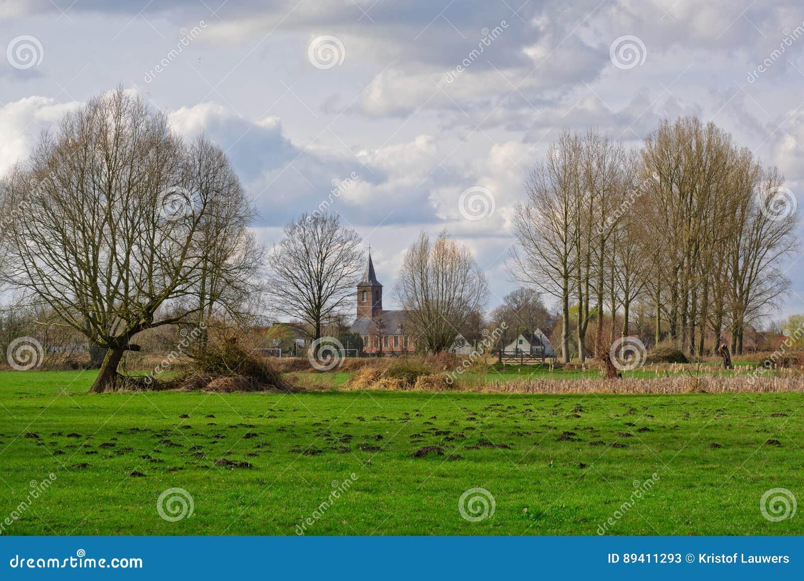 Paisagem flamenga do famland com igreja