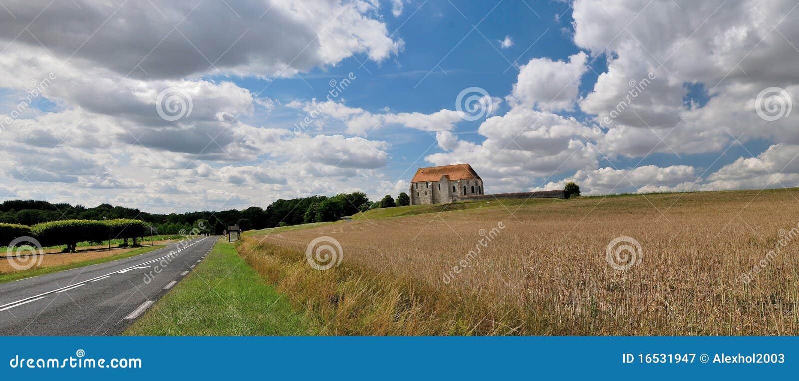 A paisagem francesa com igreja rural.