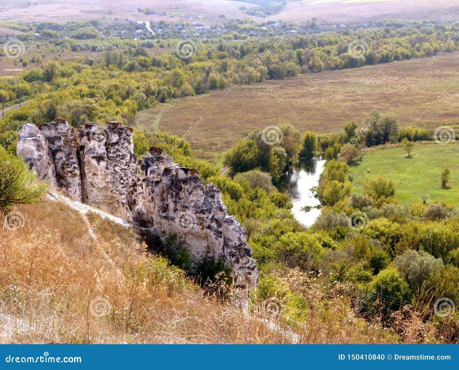 Paisagem lindo com rio, árvores e montanhas do giz