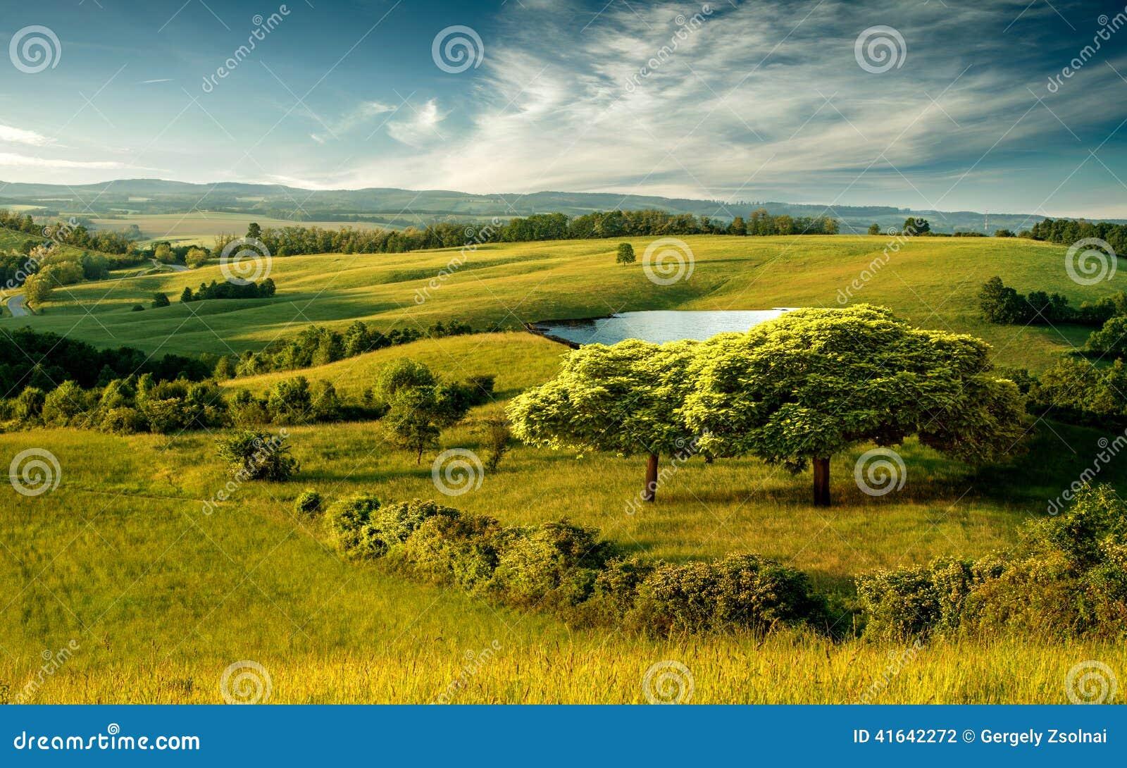 Paisagem montanhosa bonita com lago e o céu nebuloso azul
