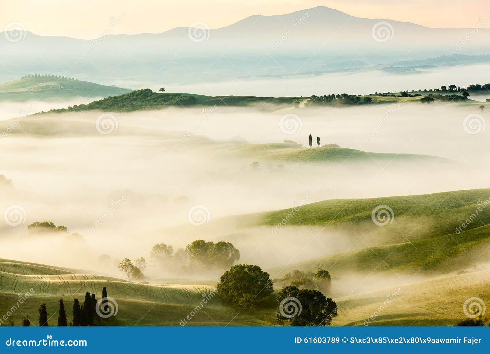 A paisagem nevoenta do conto de fadas de Tuscan coloca no nascer do sol