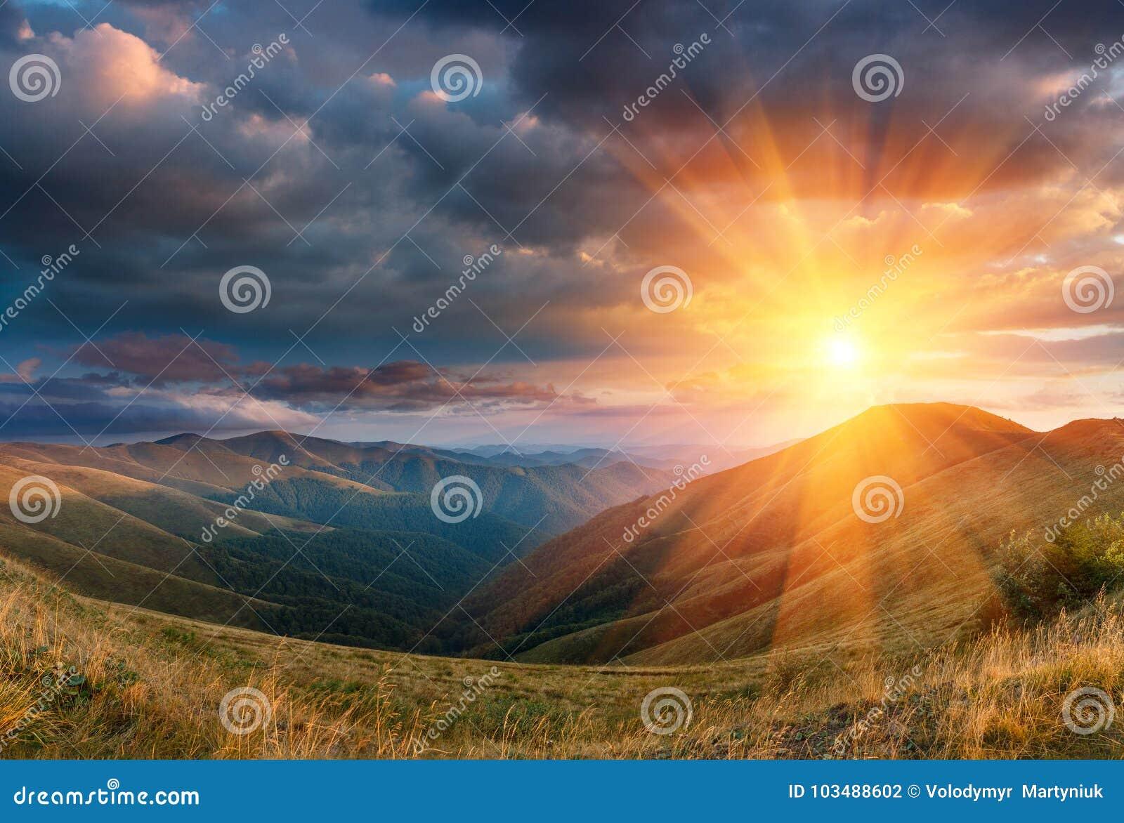 Paisagem panorâmico do por do sol fantástico nas montanhas A vista dos montes do outono iluminou-se pelos raios do sol da noite