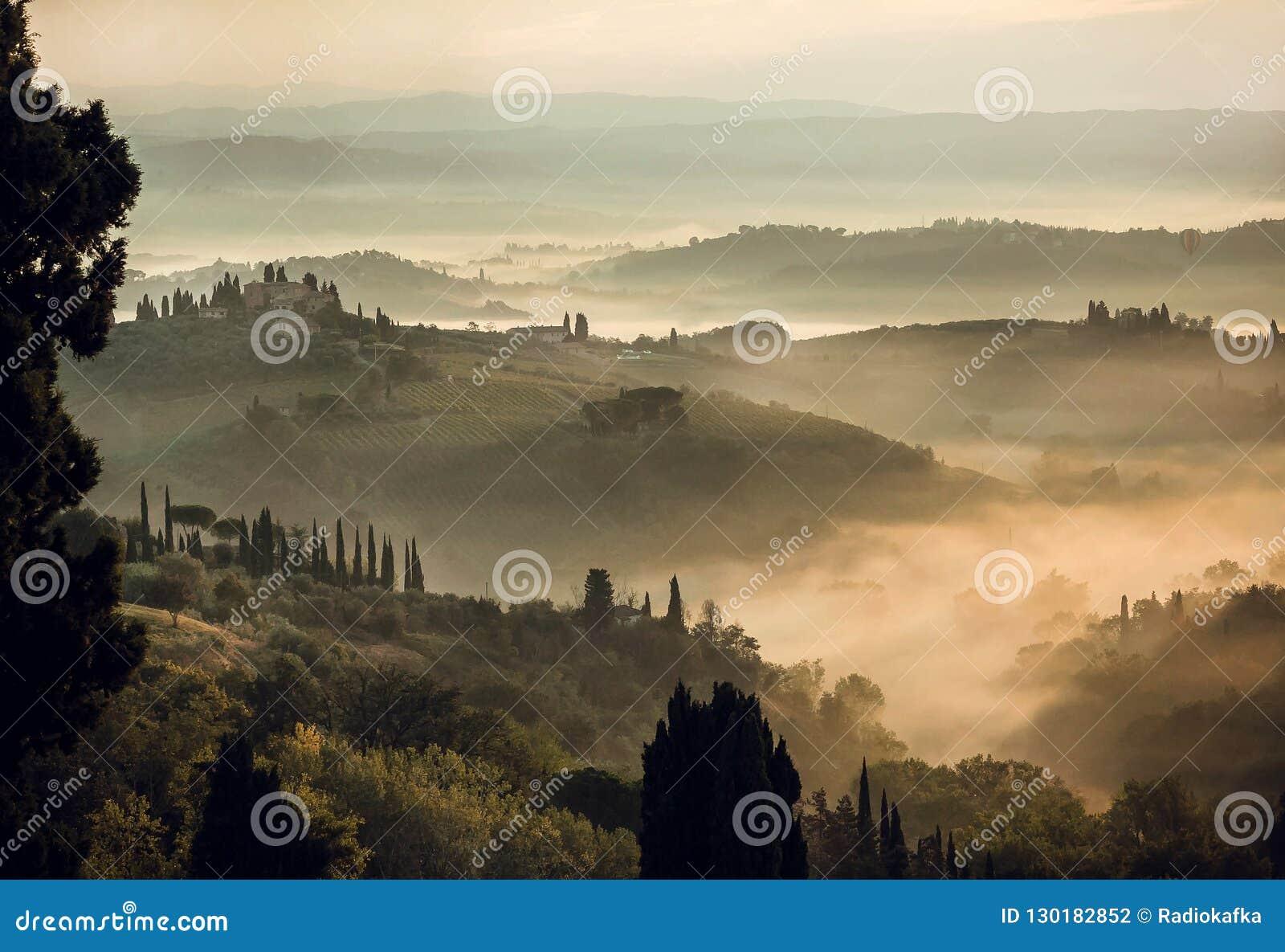 Paisagem rural no nascer do sol enevoado Montes de Toscânia com árvores do jardim, casas de campo, montes verdes, campo, Itália