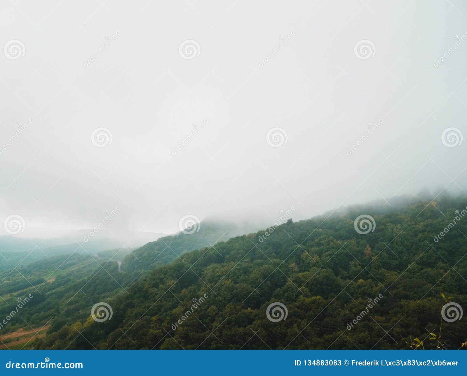 Paisagem temperamental: terreno montanhoso coberto nas nuvens e na névoa