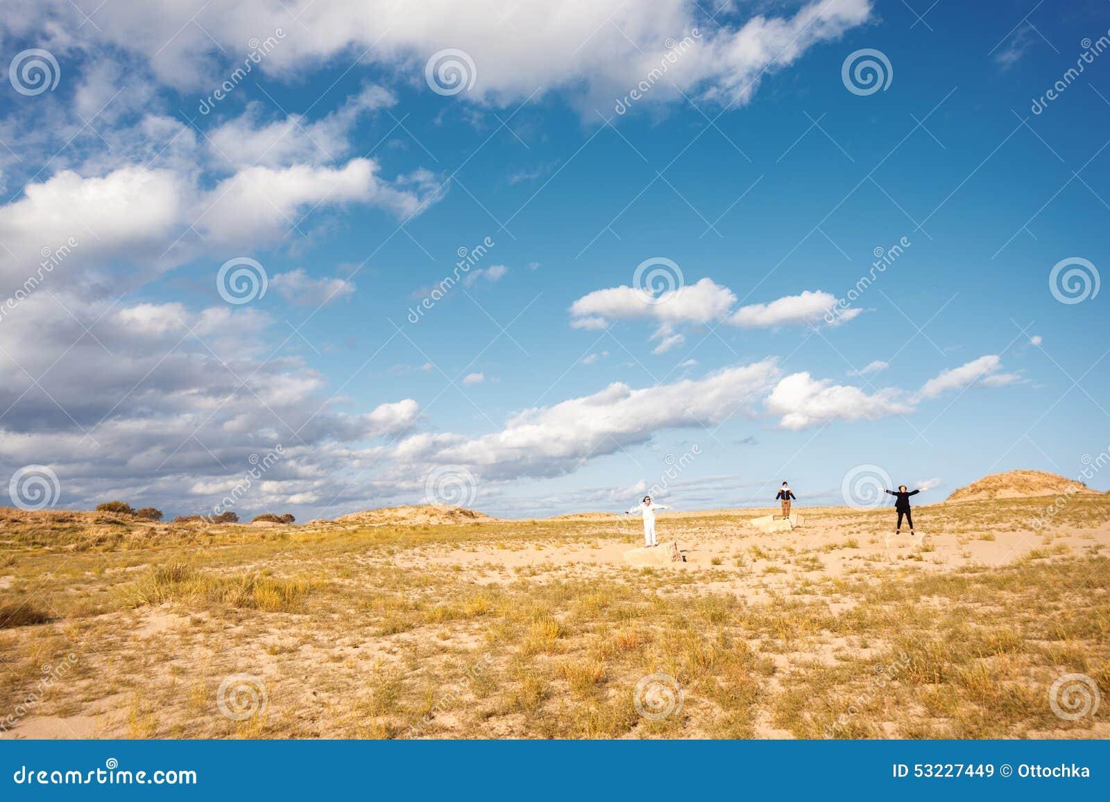 Paisaje con la gente Tres personas que se colocan en un campo en las rocas con los brazos aumentados