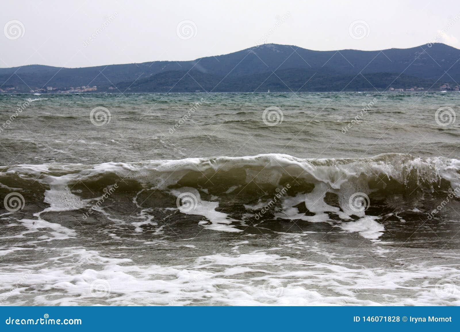 Paisaje con las ondas y las monta?as en la isla