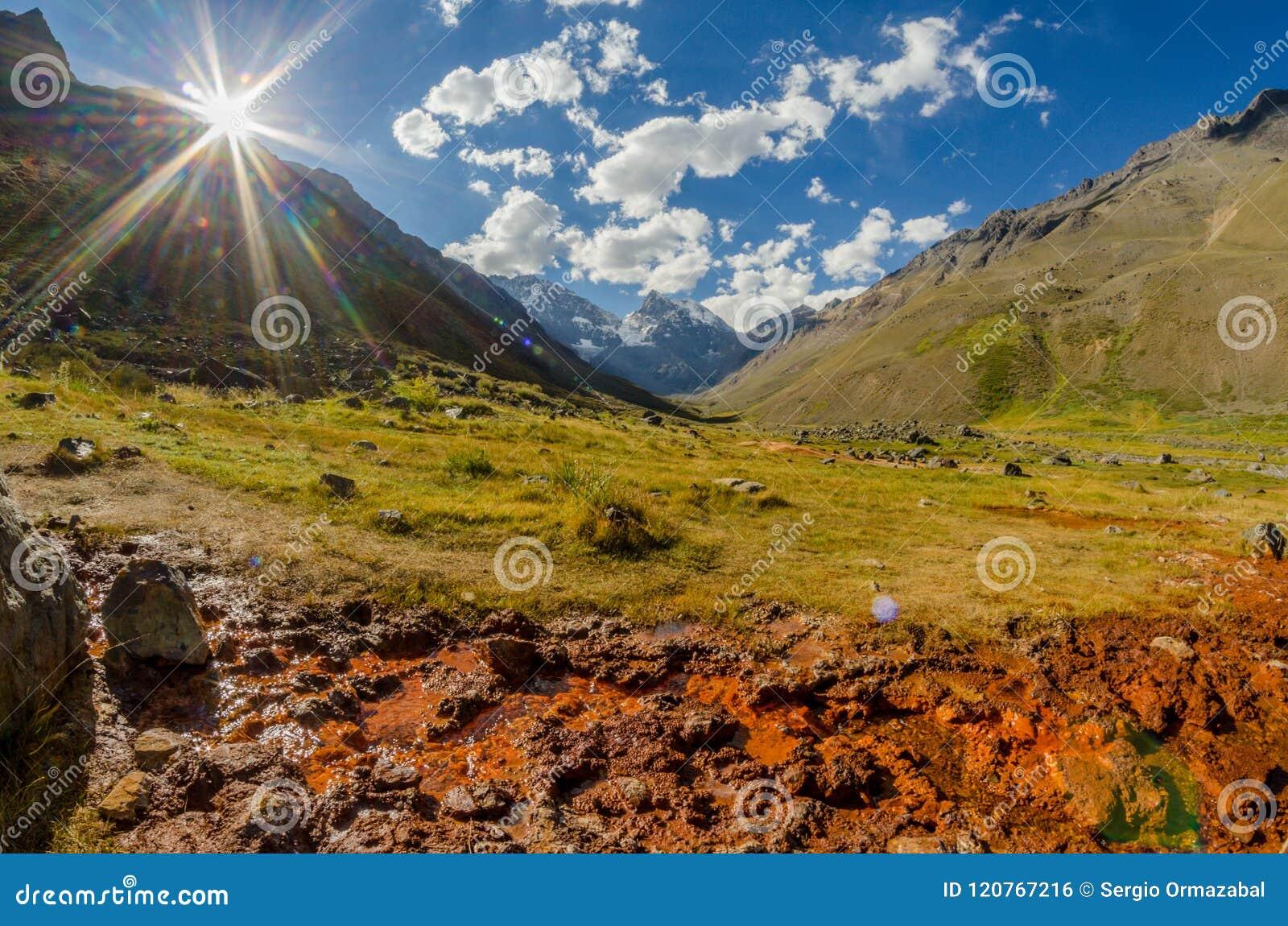 Paisaje de la cordillera con el valle verde iluminado por la luz del sol, el cielo azul con las nubes y un pequeño canal de agua