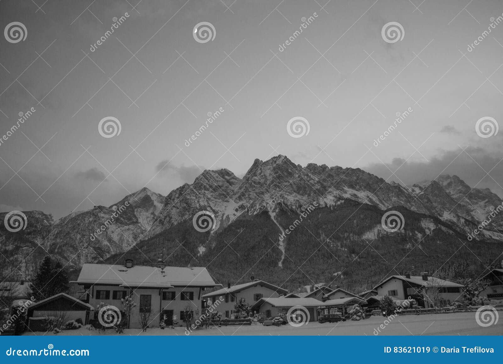 Paisaje de la montaña con el macizo y el pueblo de la montaña en invierno en la noche