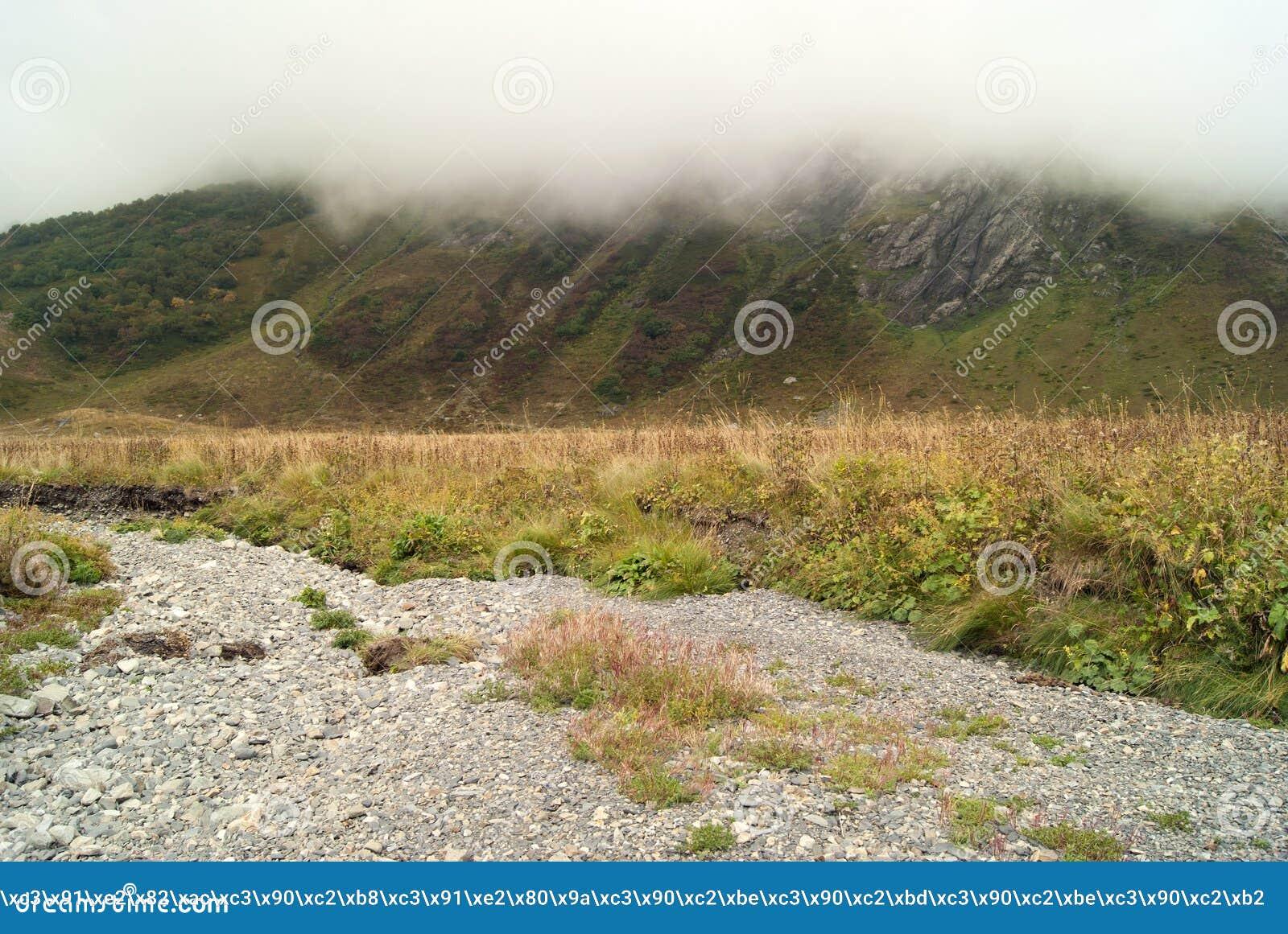 Paisaje de la montaña con un canal seco y una montaña ocultados por una nube en el fondo,