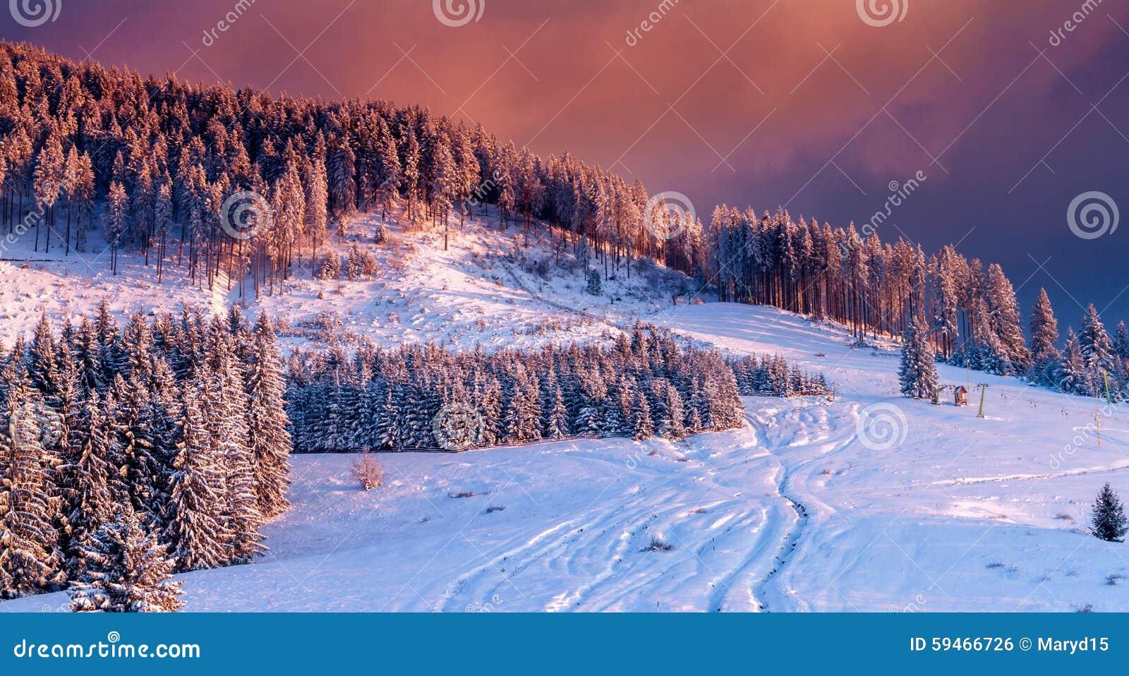 Paisaje de la montaña en el invierno, cubierto con nieve, con una puesta del sol colorida que cubre la escena entera en colores c
